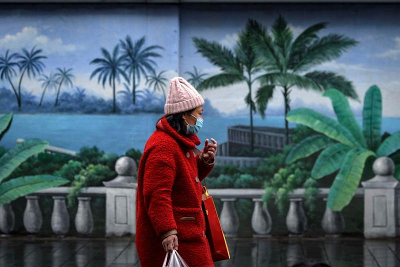 WUHAN, CHINA - FEBRUARY 28 2020: A pedestrian walks by a painted wall in Wuhan in central China's Hubei province Friday, Feb. 28, 2020.