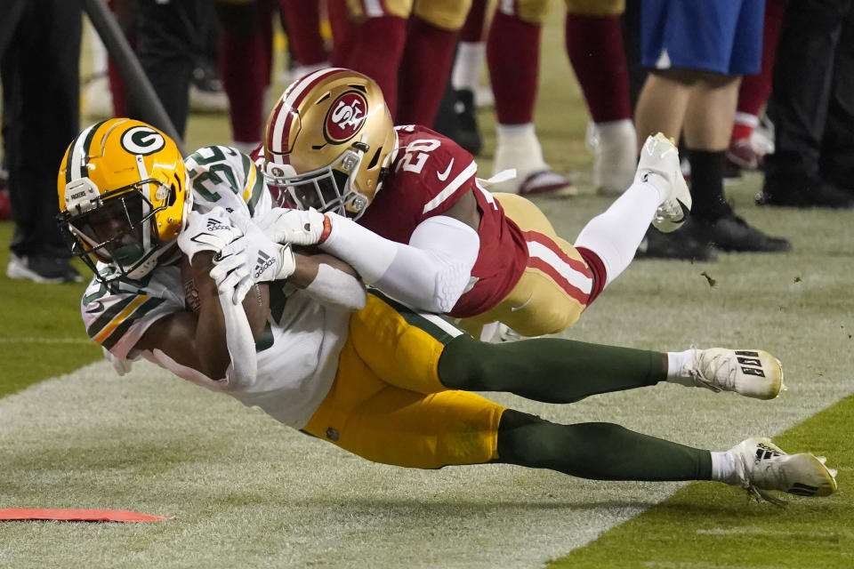 Green Bay Packers running back Tyler Ervin (32) is tackled by San Francisco 49ers free safety Jimmie Ward (20) during the first half of an NFL football game in Santa Clara, Calif., Thursday, Nov. 5, 2020. (AP Photo/Tony Avelar)