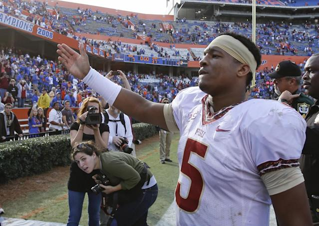 Florida State quarterback Jameis Winston does the tomahawk chop for fans as he comes off the field after defeating Florida 37-7 in an NCAA college football game in Gainesville, Fla., Saturday, Nov. 30, 2013. (AP Photo/John Raoux)