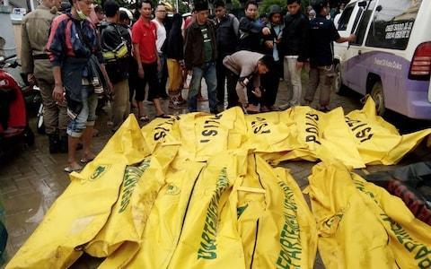 Bodies of victims recovered along Carita beach are placed in body bags - Credit: AFP