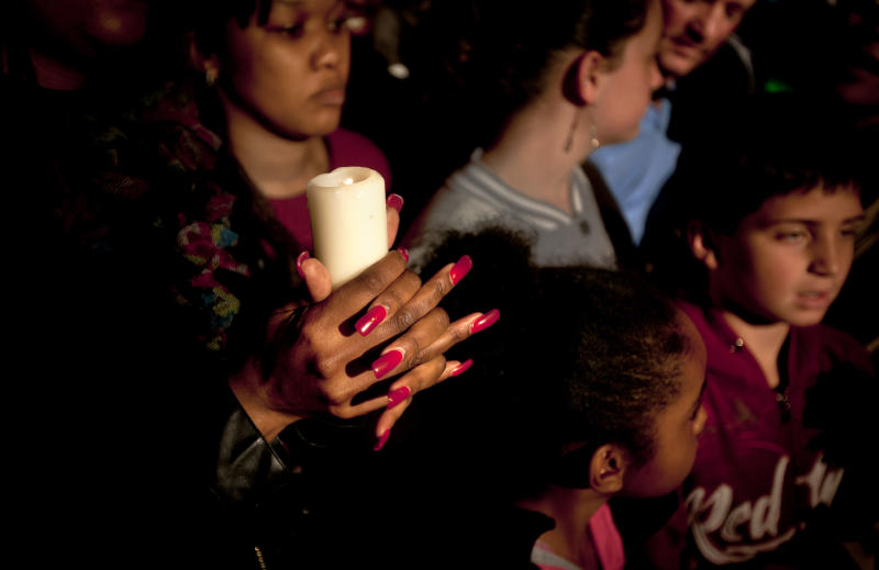 A woman from a community group based in Pretoria holds a candle and sings religious songs to show appreciation and support for former South African President, Nelson Mandela, on the street outside the Mediclinic Heart Hospital where he is being treated in Pretoria, South Africa Tuesday, June 25, 2013. South Africa's president Jacob Zuma on Tuesday urged his compatriots to show their appreciation for Nelson Mandela, who is in critical condition in a hospital, by marking his 95th birthday next month with acts of goodness that honor the legacy of the anti-apartheid leader. (AP Photo/Ben Curtis)