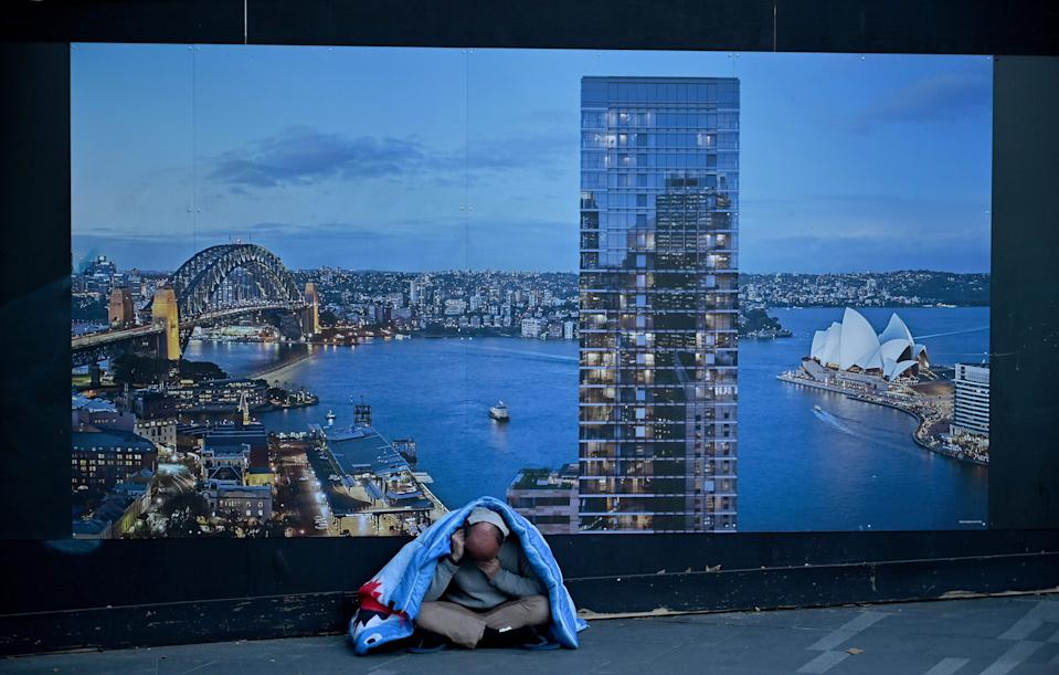 A homeless man sits in front of a billboard by a construction site in Sydney on July 24, 2019. (Photo by PETER PARKS / AFP)        (Photo credit should read PETER PARKS/AFP via Getty Images)