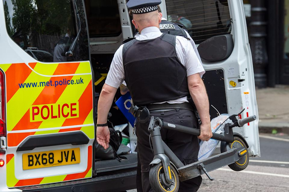 A police officer places a confiscated electric scooter in a police van after he stopped a man for riding it in London. (PAN)