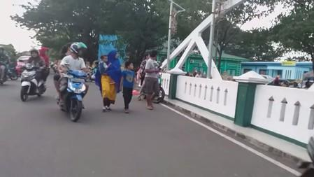 People look over a bridge as they flee after an earthquake in Ternate