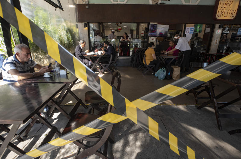 ASSOCIATED PRESS - People eat lunch at a restaurant that reopened with limited entrances amid the COVID-19 pandemic in Sao Paulo, Brazil, Monday, July 6, 2020. Bars, restaurants and beauty salons were allowed to re-open Monday after over three months of quarantine, and are required to observe preventative measures and reduced operating hours only during the day. (AP Photo/Andre Penner)