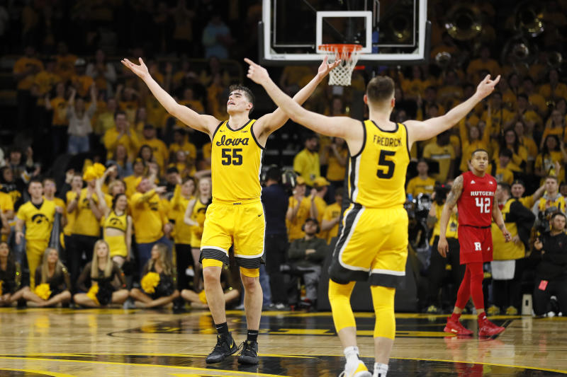 Iowa's Luka Garza (55) and CJ Fredrick (5) celebrate in front of Rutgers' Jacob Young (42) at the end of an NCAA college basketball game, Wednesday, Jan. 22, 2020, in Iowa City, Iowa. Iowa won 85-80. (AP Photo/Charlie Neibergall)