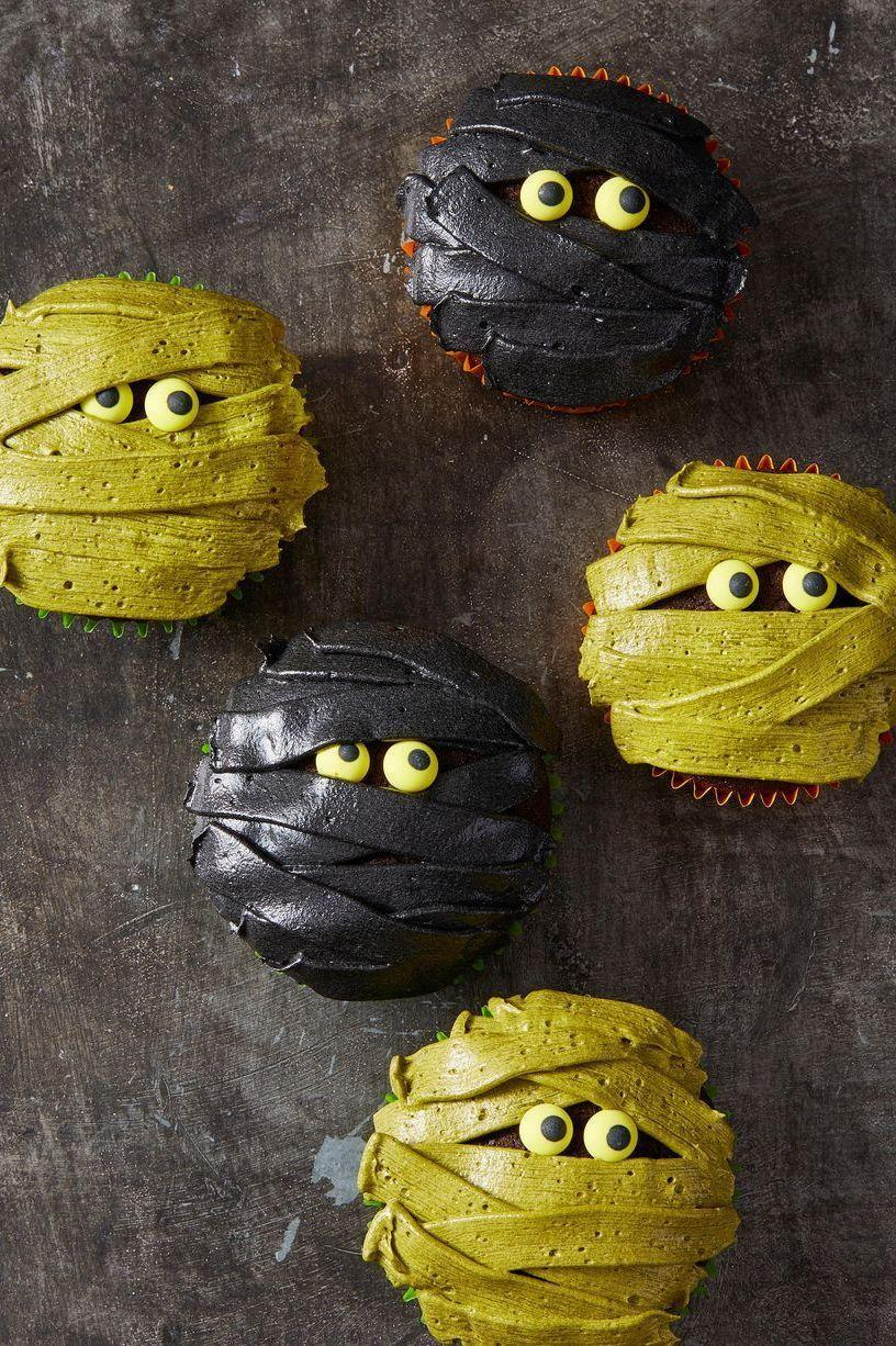"""<p>Peep these wrapped cupcakes decorated with sweet vanilla cupcakes. </p><p><em><a href=""""https://www.goodhousekeeping.com/food-recipes/party-ideas/a28593338/mummy-cupcakes-recipe/"""" rel=""""nofollow noopener"""" target=""""_blank"""" data-ylk=""""slk:Get the recipe for Mummy Cupcakes »"""" class=""""link rapid-noclick-resp"""">Get the recipe for Mummy Cupcakes »</a></em></p>"""