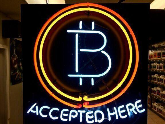A neon sign hanging in the window of Healthy Harvest Indoor Gardening in Hillsboro, Ore., shows that the business accepts bitcoin as payment. Photo: AP Photo/Gillian Flaccus, File.
