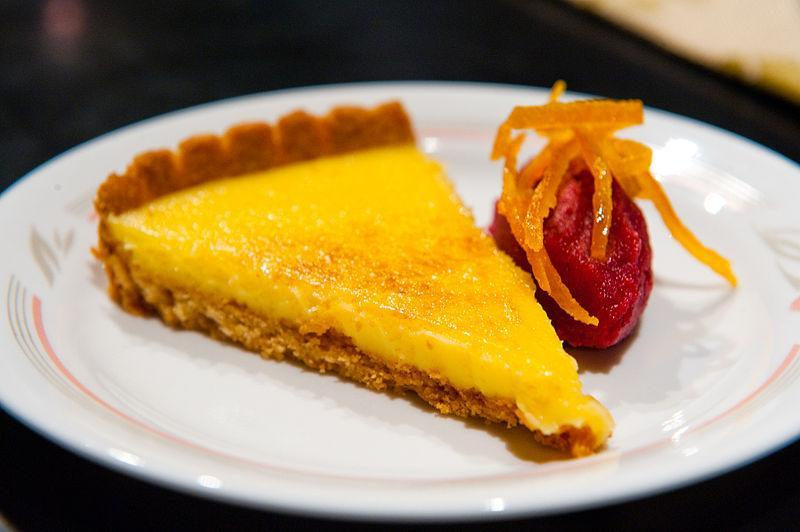 """<p>An easy no bake lemon curd tart will jazz up your dinner tables without too much fuss. To make the tart, mix 200 gms processed crumbs of marie biscuits with 100 gms melted unsalted butter & some cinnamon powder to taste. Combine well & place in a round pan that has been generously greased with some butter. Press gently so that the mix covers the sides of the pan too. Refrigerate for 1 to 2 hours till set. To make lemon curd, mix together 3 eggs with 3/4th cup sugar & whisk in a bowl. Now heat the mix in the bowl with a double boiler method & keep stirring as you add juice of 2-3 lemons. Keep cooking till the lemon curd reaches custard like consistency, remove from flame & add 3-4 tsp unsalted butter & mix well. Pour the lemon curd into the chilled tart base once it cools down a bit & chill in refrigerator till set. Cut into slices & serve. """"Creative Commons A lemon Tart"""" by John is licensed under CC BY 2.0 </p>"""