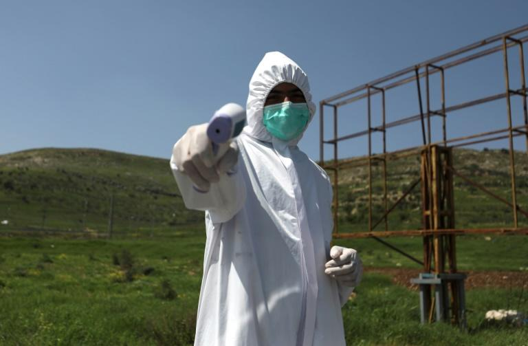 Palestinian civilians are deployed along rural roads in the occupied West Bank to enforce coronavirus controls amid the COVID-19 pandemic