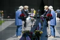 Masked visitors to the Vietnam Memorial pay respects in Washington