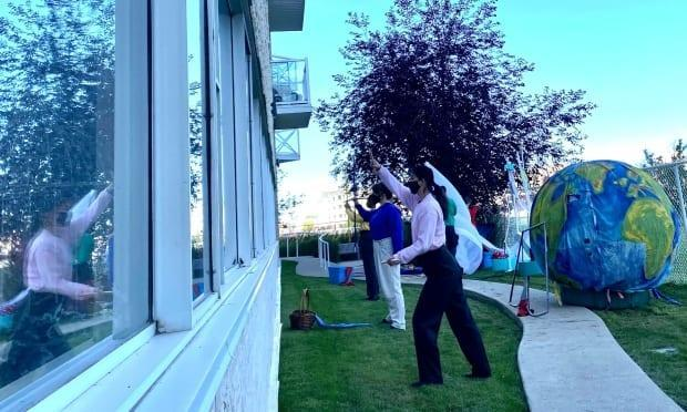 Sum Theatre group performed their show Through the Window outside a long-term care home in Regina on Thursday. (Ricardo Alvarado - image credit)