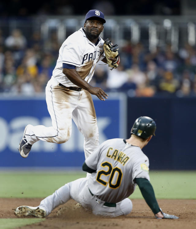 San Diego Padres second baseman Jose Pirela forces out Oakland Athletics' Mark Canha at second base, then watches as Stephen Piscotty is called out at first, for a double play, with Khris Davis scoring, during the second inning of a baseball game in San Diego, Tuesday, June 19, 2018. (AP Photo/Alex Gallardo)