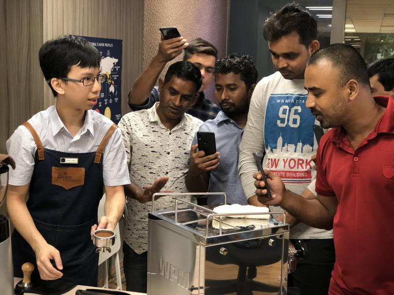 The Coffee Roaster founder Ang Swee Heng, 26, shows Bangladeshi migrant workers the ropes of brewing gourmet coffee. PHOTO: Nicholas Yong/Yahoo News Singapore