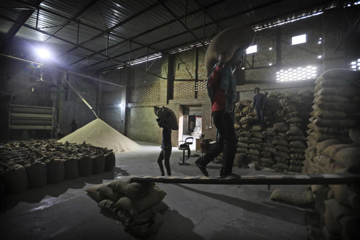 Laborers stack rice in a private warehouse in Makhu, in the Indian state of Punjab, Friday, March 12, 2021. India's water crisis looms over the agrarian crisis that has been brewing for decades. And at its heart is a policy conundrum: India has been subsidizing the cultivation of rice in northern India, but these are thirsty crops that have depleted the ground water. (AP Photo/Manish Swarup)