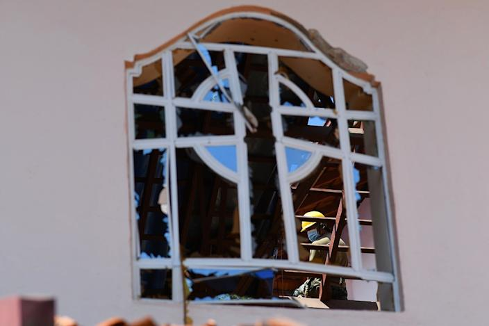 A worker clears debris from the roof of St. Sebastian's Church in Negombo on April 22, 2019, a day after the church was hit in series of bomb blasts targeting churches and luxury hotels in Sri Lanka. (Photo: Jewel Samad/AFP/Getty Images)