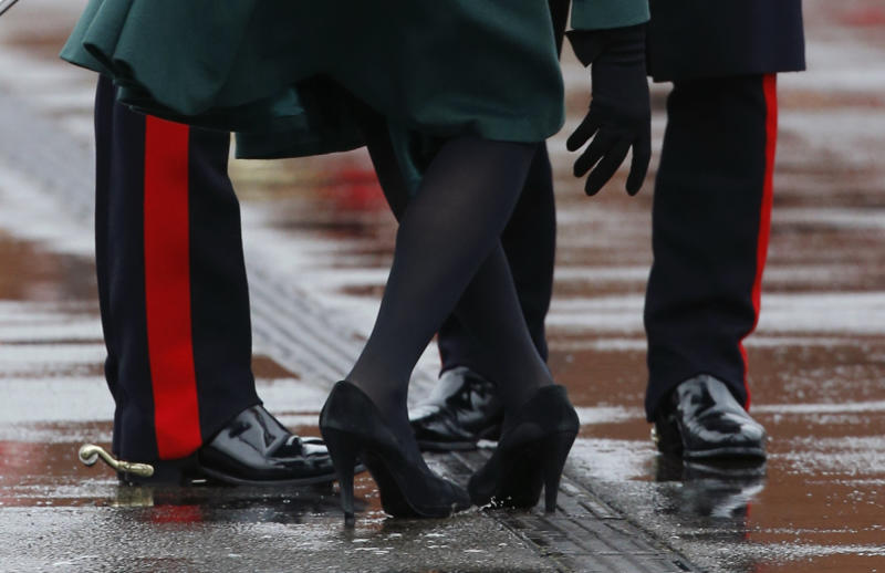 Britain's Kate Duchess of Cambridge holds onto the hand of her husband Prince William, left, as she bends down to pull the heel of her shoe out of a drainage grill after it got stuck, as she presents the traditional sprigs of shamrock to members of the 1st Battalion Irish Guards at the St Patrick's Day Parade at Mons Barracks in Aldershot, England, Sunday, March 17, 2013. Kate presenting the sprigs of shamrock to the regiment Sunday, follows a century-old tradition inaugurated by Queen Alexandra, the wife of the then King, Edward VII back in 1901. (AP Photo/Matt Dunham)