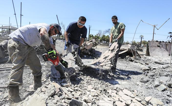 "McKenzie Fisher and Agustin Gonzalez, from left, help their friend Alvaro Baltierra clear debris from his fire-ravaged home in Niland, Calif. <span class=""copyright"">(Eduardo Contreras / San Diego Union-Tribune)</span>"