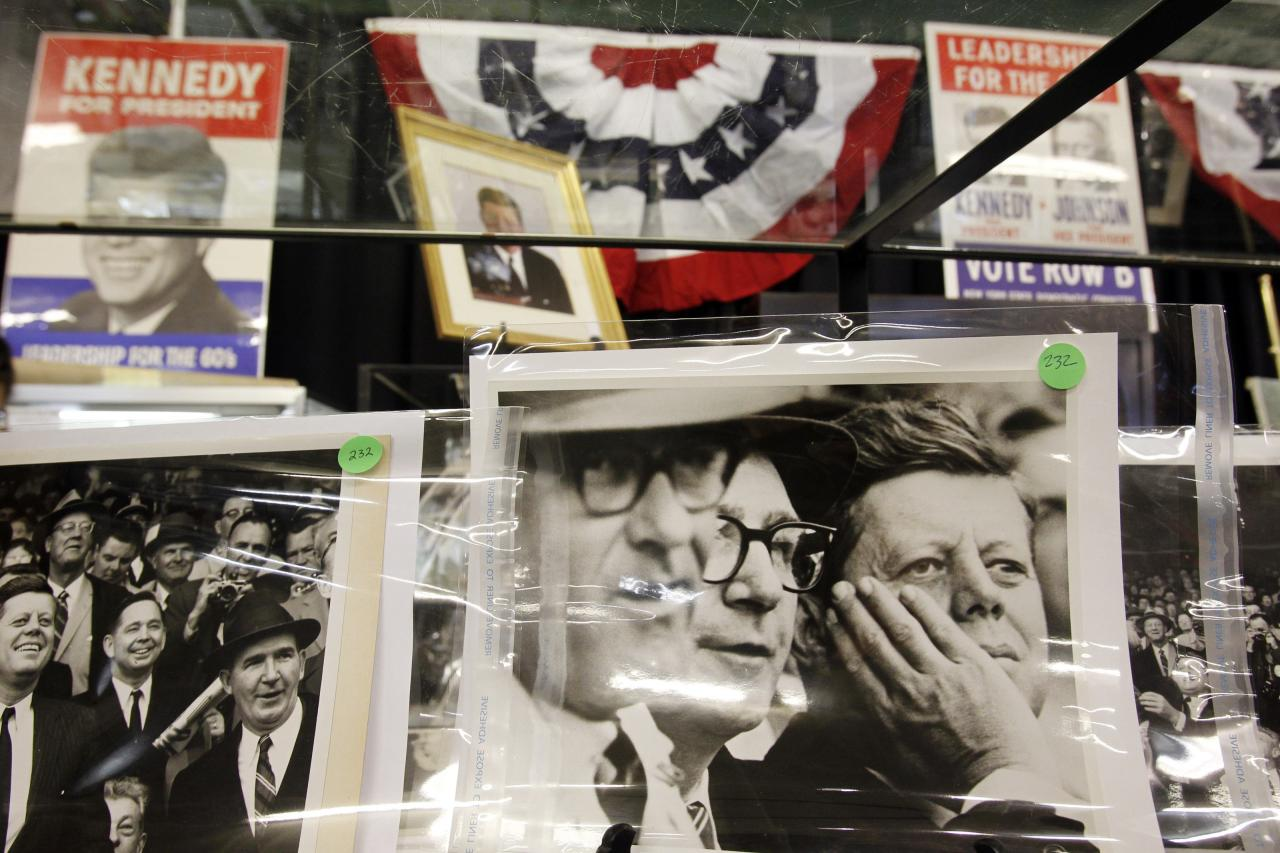 Campaign posters are just seen behind pictures of the former President (Reuters)