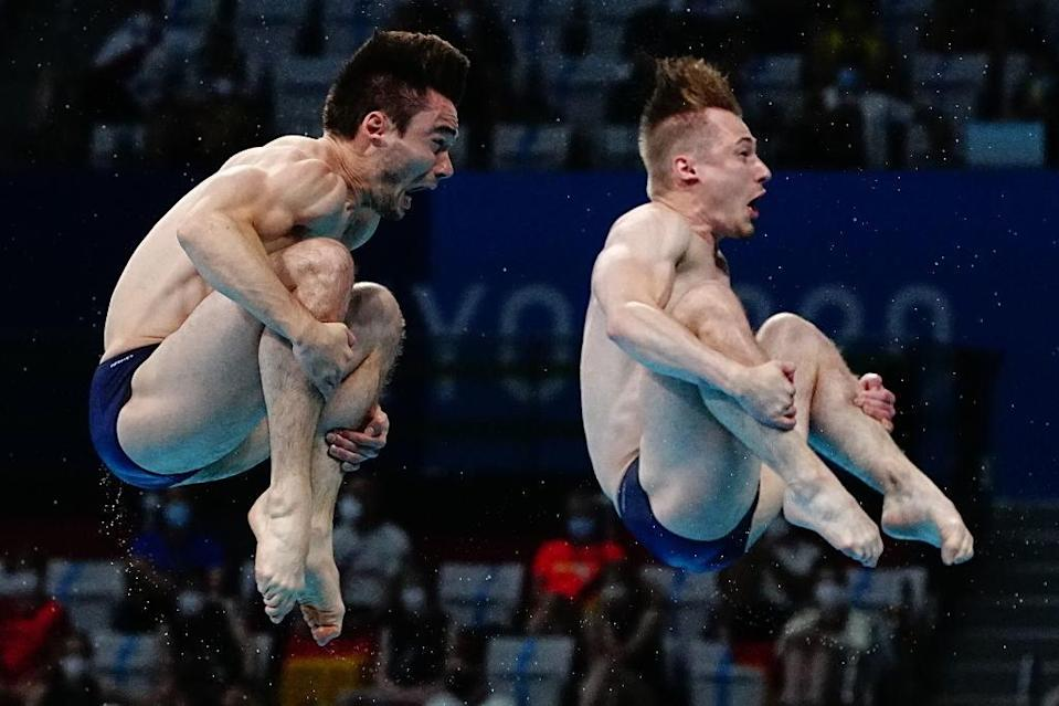 Two divers with their mouths open as they spin through the air