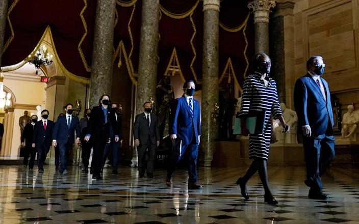 Clerk of the House Cheryl Johnson and acting House Sergeant-at-Arms Tim Blodgett lead the impeachment managers through Statuary Hall in the Capitol - AP