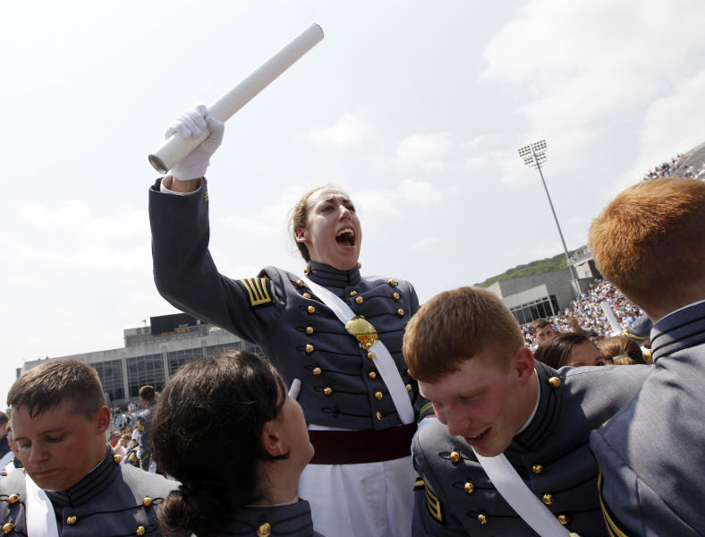 In this Saturday, May 26, 2012 photo, Kaitlyn Kelly, center, reacts after a graduation and commissioning ceremony at the U.S. Military Academy in West Point, N.Y. At West Point, the alumni gay advocacy group Knights Out was able to hold the first installment in March of what is intended to be an annual dinner in recognition of gay and lesbian graduates and cadets. Kelly was among the dozens of cadets who attended the privately sponsored dinner. The 22-year-old Chicago resident was finally able to openly introduce her civilian girlfriend at an event marking 100 days before graduation. (AP Photo/Mike Groll)