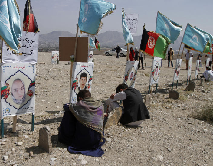 Afghan boys sit next to the grave of their classmate, adorned with this picture, on the outskirts of Kabul, Afghanistan, Monday, Sept 14, 2020. Scores of friends and families of students who were killed in local conflicts are gathering in a cemetery to call for a permanent countrywide ceasefire from the parties to the intra-Afghan peace conference taking place in Doha, Qatar. (AP Photo/Rahmat Gul)