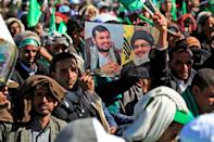 A Yemeni man holds up pictures of Huthi rebel leader Abdul Malik al-Huthi (left) and chief of the Shiite Muslim movement Hezbollah Hassan Nasrallah