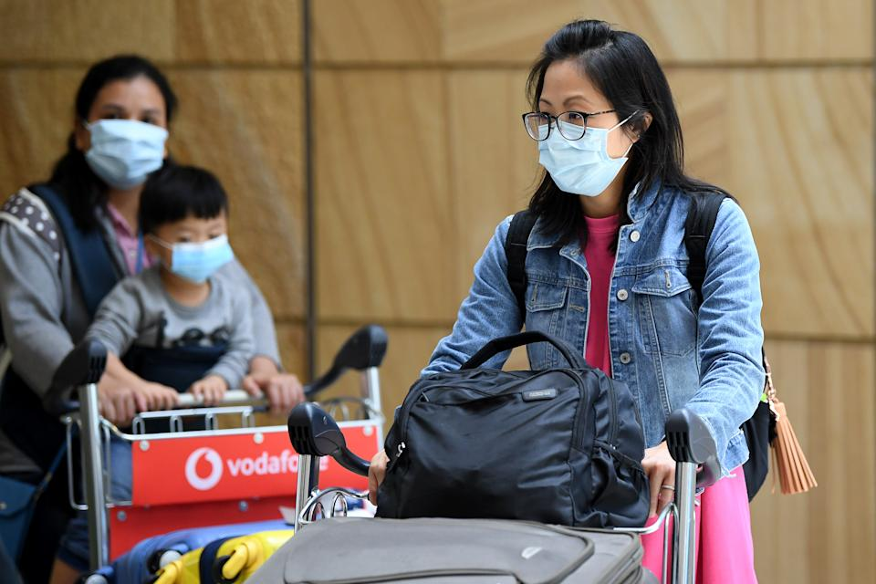 Passengers wearing protective masks arrive at Sydney International Airport in Sydney, Thursday, January 23. Source: AAP