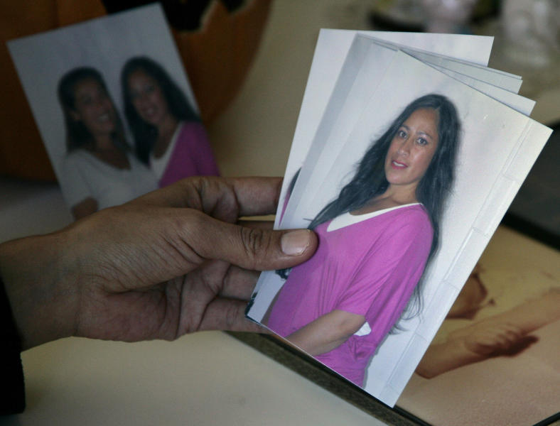 """In this Tuesday, Oct. 16, 2012 photo, Andrea Waple holds a photo of her sister, Barbara Hernandez, at her home outside of Columbiaville, Mich. Hernandez says, """"There's just so many things I could've done and mostly I'm asking myself, 'Why didn't you run? Why didn't you go to the police? Why did you just blindly go to the store? Why did you bring Mr. Cotaling into the house? Everything is whys and question marks."""" (AP Photo/Al Goldis)"""
