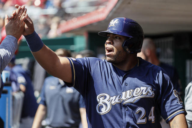 Milwaukee Brewers' Jesus Aguilar celebrates in the dugout after scoring on an RBI single by Manny Pina off Cincinnati Reds starting pitcher Luis Castillo in the second inning of a baseball game, Wednesday, April 3, 2019, in Cincinnati. (AP Photo/John Minchillo)