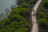 Migrants walk on a dirt road after crossing the U.S.-Mexico border, Tuesday, March 23, 2021, in Mission, Texas. (AP Photo/Julio Cortez)