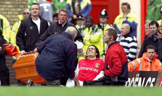 FILE PHOTO: Arsenal's French midfielder Robert Pires receives treatment after damaging his knee ligaments
