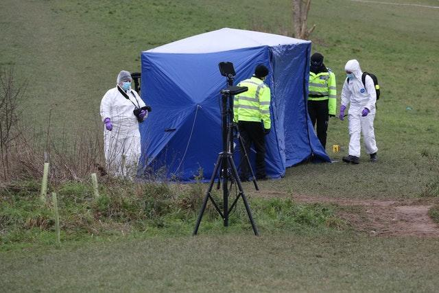 Forensic officers at the tent in Bugs Bottom field in Emmer Green, Reading, where a 13-year-old boy died after being stabbed on Sunday