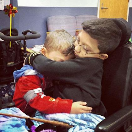 Two children hugging each other. One sits in a wheelchair