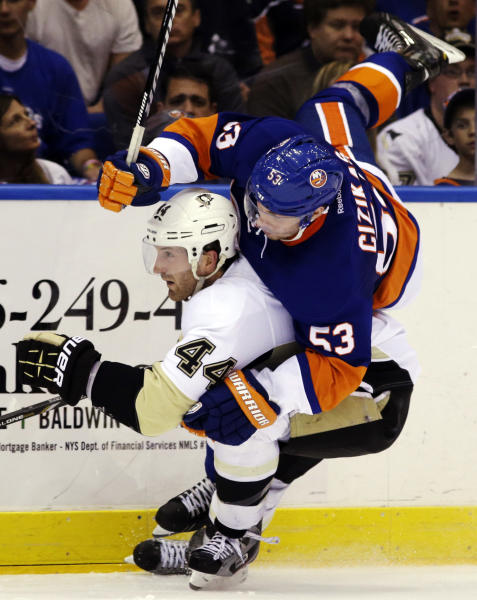 Pittsburgh Penguins defenseman Brooks Orpik (44) checks New York Islanders center Casey Cizikas (53) in the second period of Game 4 of their first-round NHL hockey Stanley Cup playoffs hockey series at Nassau Coliseum in Uniondale, N.Y., Tuesday, May 7, 2013. (AP Photo/Kathy Willens)
