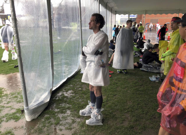 Lukas Chmatal, 35, originally from the Czech Republic and now a scientist at Massachusetts Institute of Technology, waits under a tent while it rains before the start of the 123rd Boston Marathon on Monday, April 15, 2019, in Hopkinton, Mass. (AP Photo/Jennifer McDermott)