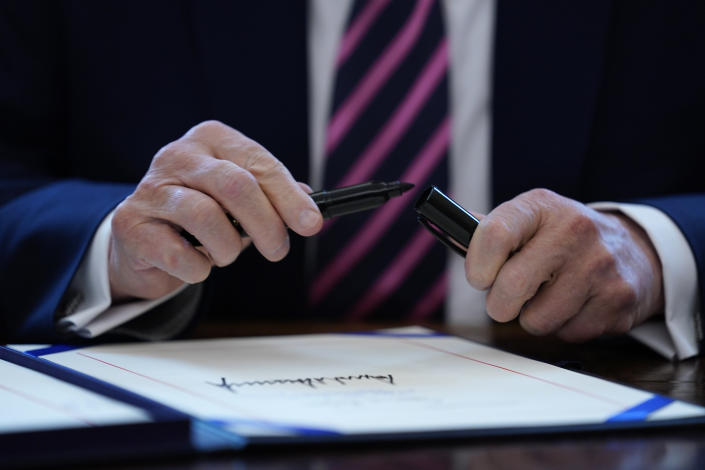 FILE - In this April 24, 2020, file photo President Donald Trump puts the cap on a pen after signing a coronavirus aid package to direct funds to small businesses, hospitals, and testing, in the Oval Office of the White House in Washington. (AP Photo/Evan Vucci, File)