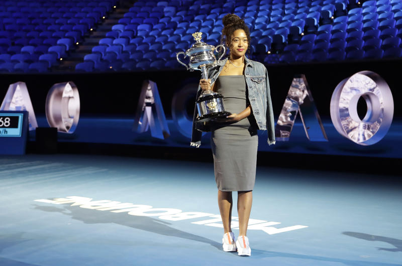 Defending woman's singles champion Japan's Naomi Osaka holds the Daphne Ackhurst Cup following the official draw ceremony on Margaret Court Arena ahead of the Australian Open tennis championship in Melbourne, Australia, Thursday, Jan. 16, 2020. (AP Photo/Mark Baker)