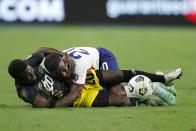Jamaica defender Kemar Lawrence (20) is knocked down by United States defender Shaq Moore, top, as the two compete for control of the ball in the second half of a CONCACAF Gold Cup quarterfinals soccer match, Sunday, July 25, 2021, in Arlington, Texas. (AP Photo/Brandon Wade)