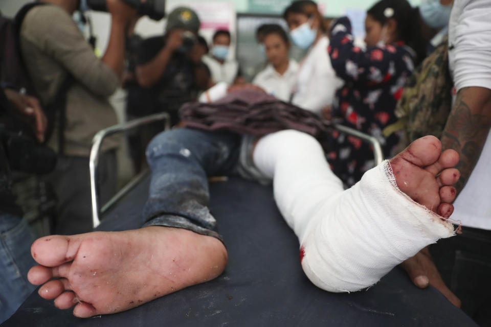 An injured protester receives medical treatment during a demonstration against the military coup in Mandalay, Myanmar, Friday, Feb. 26, 2021. (AP Photo)