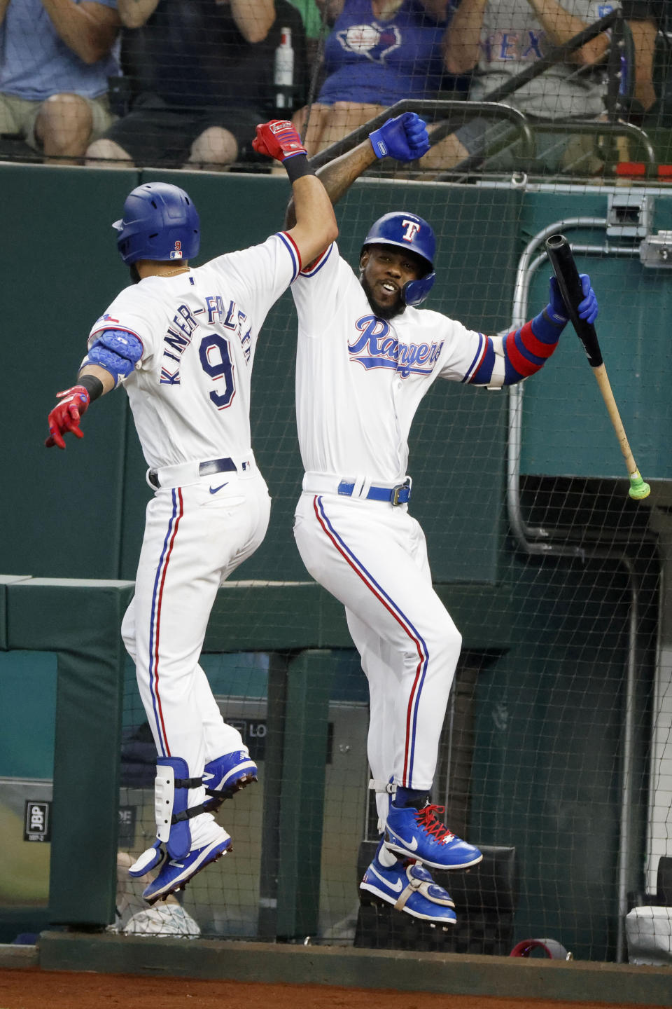 Texas Rangers' Isiah Kiner-Falefa (9) celebrates his two-run home run against the Minnesota Twins with Adolis Garcia, right, during the third inning of a baseball game Saturday, June 19, 2021, in Arlington, Texas. (AP Photo/Michael Ainsworth)