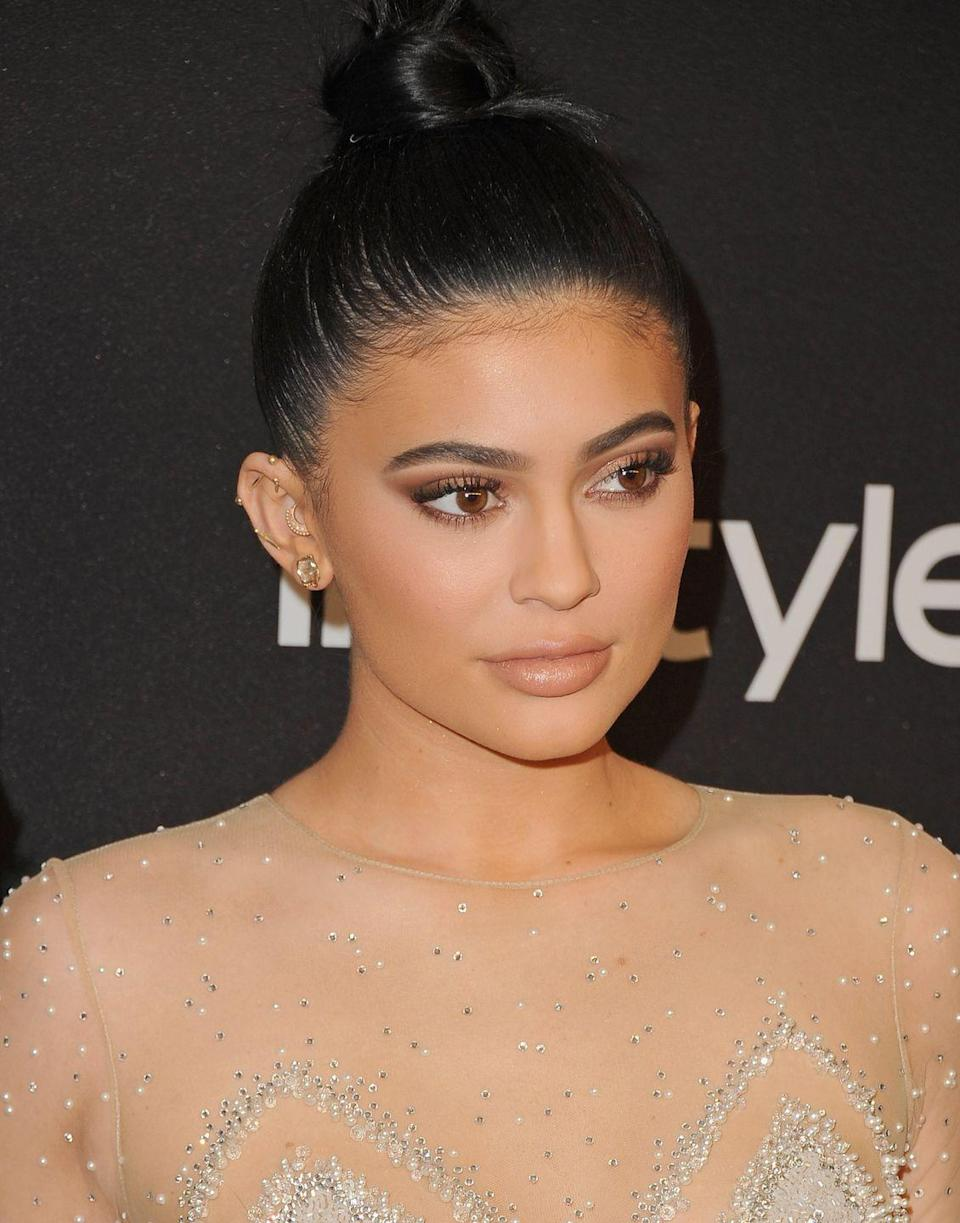 <p>Kylie's industrial looks so glam next to her snug bar stud and daith hoop earring tucked inside her ear, every spot is covered in gold. </p>