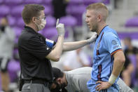 New York City FC defender Anton Tinnerholm, right, is checked by a member of the training staff after colliding with an Orlando City player during the second half of an MLS soccer playoff match, Saturday, Nov. 21, 2020, in Orlando, Fla. (AP Photo/Phelan M. Ebenhack)