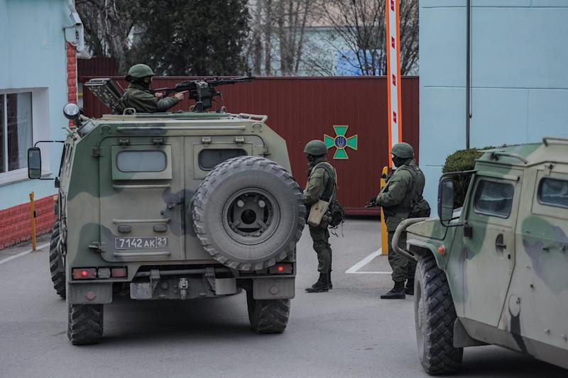 Troops in unmarked uniforms stand guard as they take control the Coast Guard offices in Balaklava on the outskirts of Sevastopol, Ukraine, Saturday, March 1, 2014. An emblem on one of the vehicles and their number plates identify them as belonging to the Russian military. Ukrainian officials have accused Russia of sending new troops into Crimea, a strategic Russia-speaking region that hosts a major Russian navy base. (AP Photo/Andrew Lubimov)