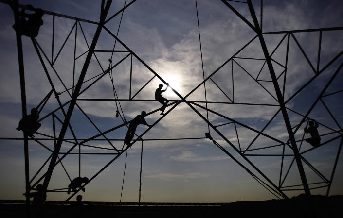 In this photo taken August 2011, workers fix an electrical power transmission tower in near the Sports City under construction in Greater Noida, India. The Indian car racing fraternity is banking on the Budh International Circuit near New Delhi to kick off a mass following for motor sports with its maiden Formula 1 race this year. Even as workers slog overtime to get the venue in shape, officials are growing confident of the event on Oct. 30 changing the face of car racing in India, a country of 1.2 billion where cricket reigns and other sports take a backseat. (AP Photo/Gurinder Osan)