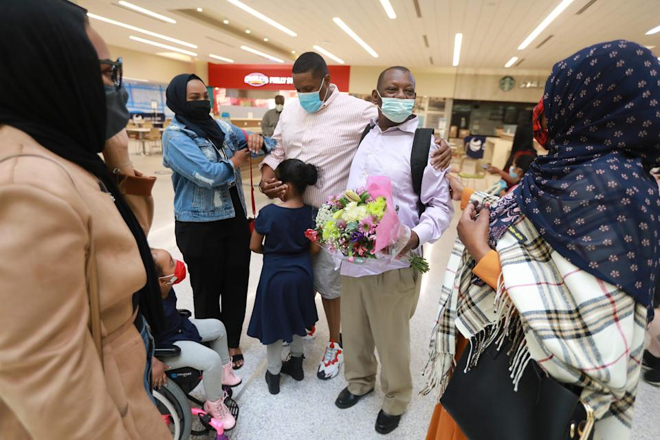 "Mohamed Salem Ali admires his family moments after arriving at John Glenn International Airport in Columbus. From left is daughter Sabah Salem, 25, granddaughter Rahaf Mohammed, 5, daughter Afnan Salem, 22, son Abdelrauuf Salem, 29, granddaughter Reem Mohammed, 6, and wife Fadumo Hussien. After 11 years apart, Ali, a Somali man living in Malaysia, wasn't able to join his family in Columbus due to the Trump administration's ""Muslim ban."" When Biden lifted the ban earlier this year, the family got their father a visa and he arrived in Columbus Thursday morning, April 8, 2021."