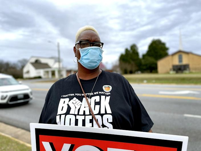 A woman in a Black Voters Matter shirt holds a sign.