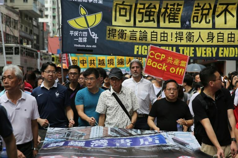 Lam Wing-kee (C-in cap), defied Beijing by speaking out about his detention and leading a protest in Hong Kong on June 18, 2016, as pressure grows for authorities to answer questions over his case