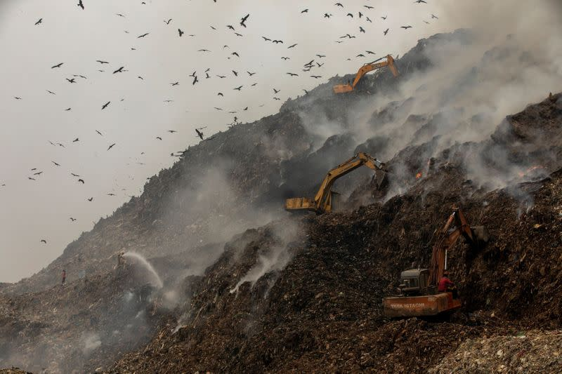 Firefighters and excavators try to douse fire as smoke billows from burning garbage at the Ghazipur landfill site in New Delhi